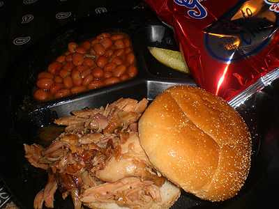 Pulled chicken sandwich, pinto beans and potato chips from Pit To Plate BBQ